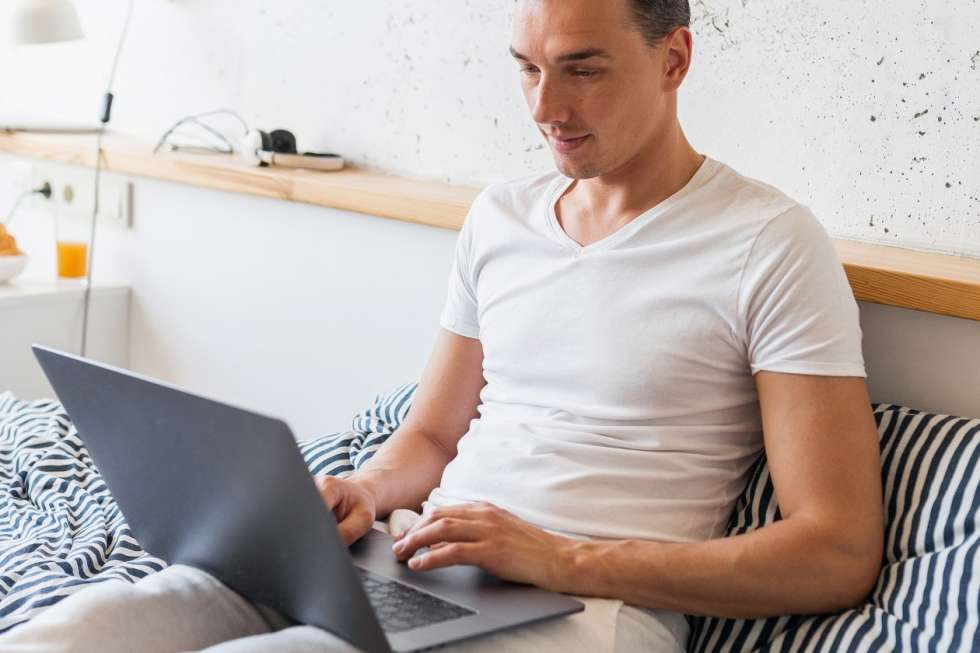 young man in casual pajamas outfit sitting in bed in morning working on laptop, busy freelancer at home